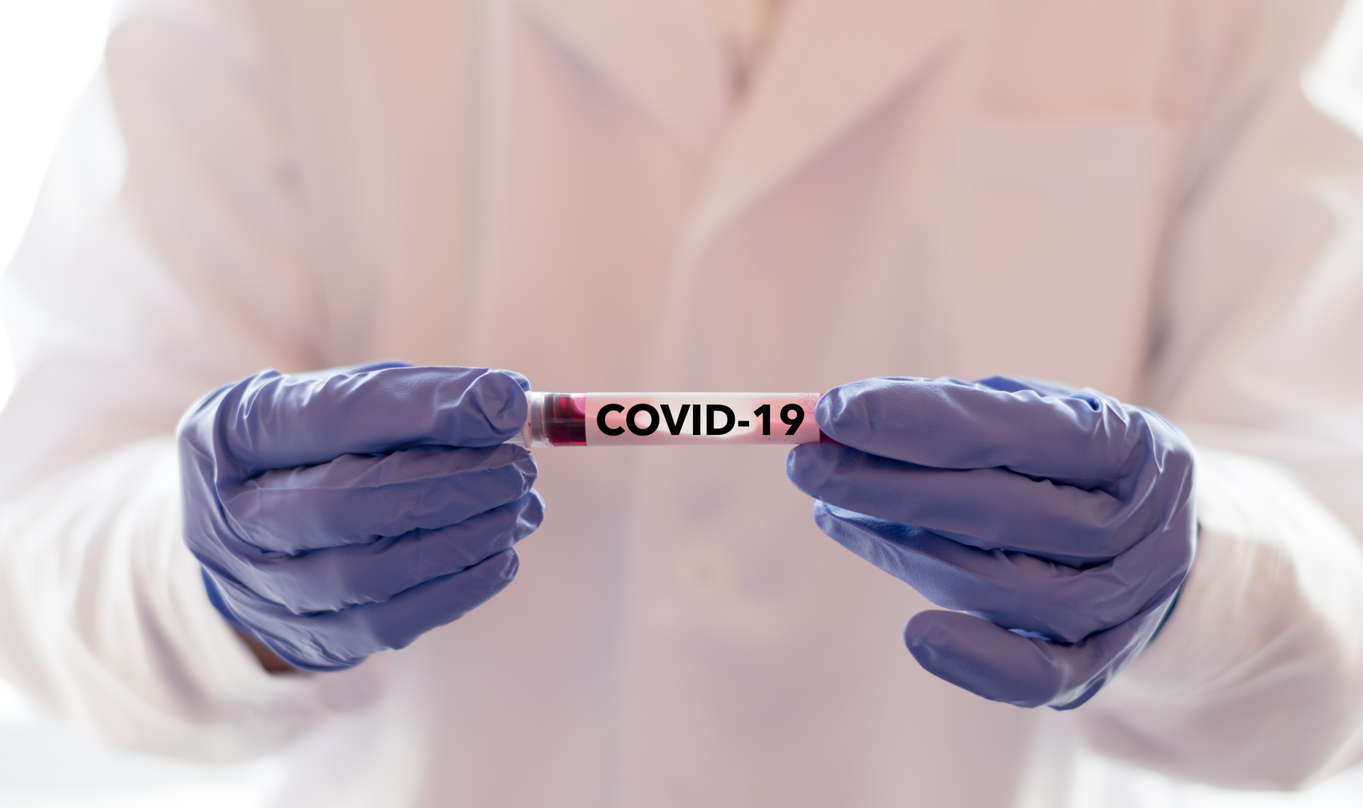 medical worker holding covid 19 vial
